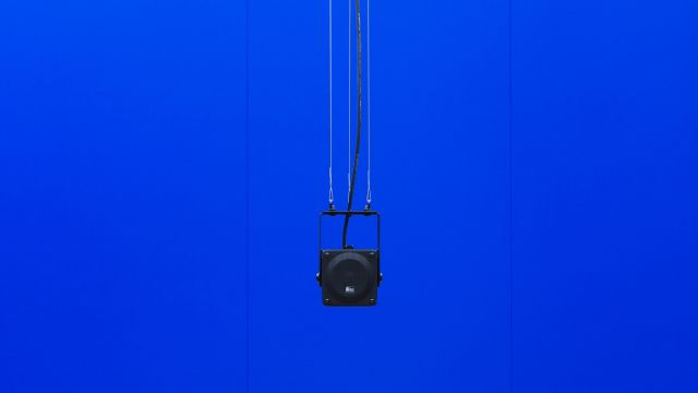 A black speaker hanging in front of a solid blue wall.