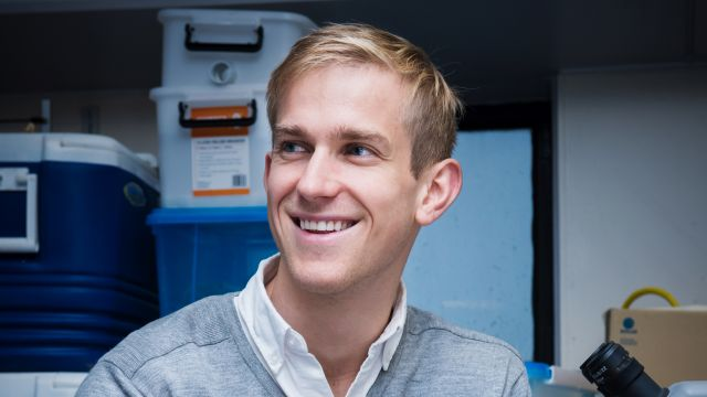 Evan looks off past the camera, smiling. Behind him are storage boxes and the top of a microscope.