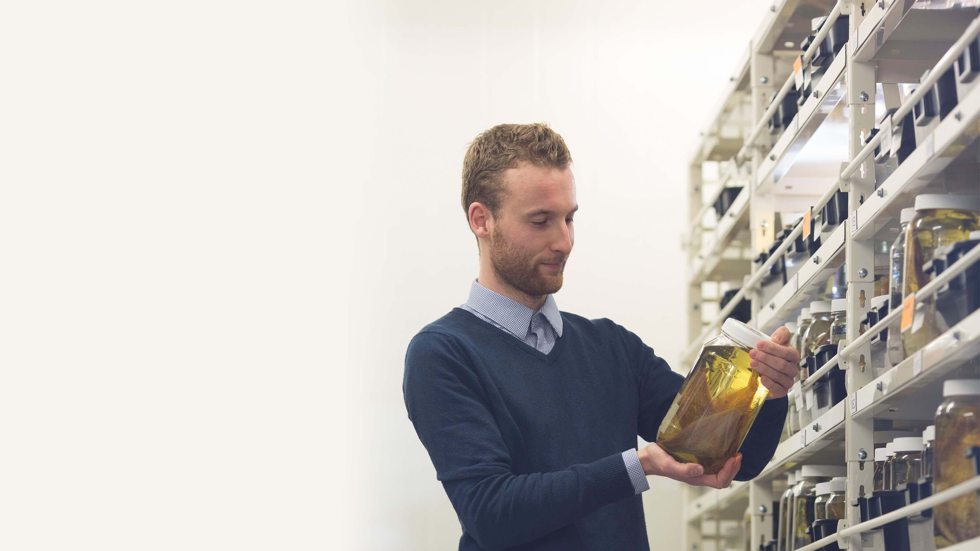 Postgraduate student looking at a specimen jar in the Victoria University Coastal Ecology Lab