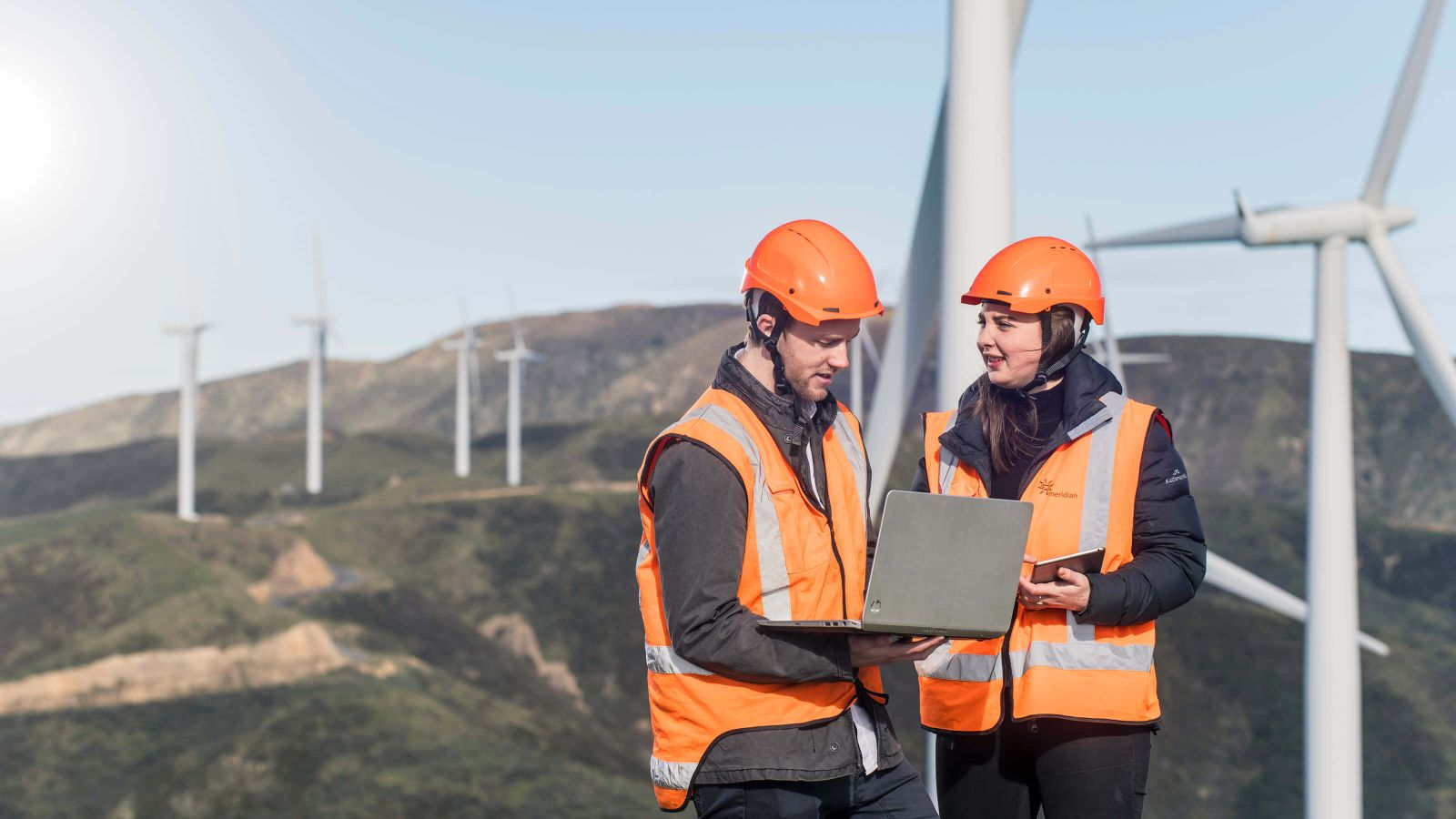 Two Engineering students, wearing safety equipment, are conducting a study while standing on a hill at the West Wind farm in Makara, Wellington.