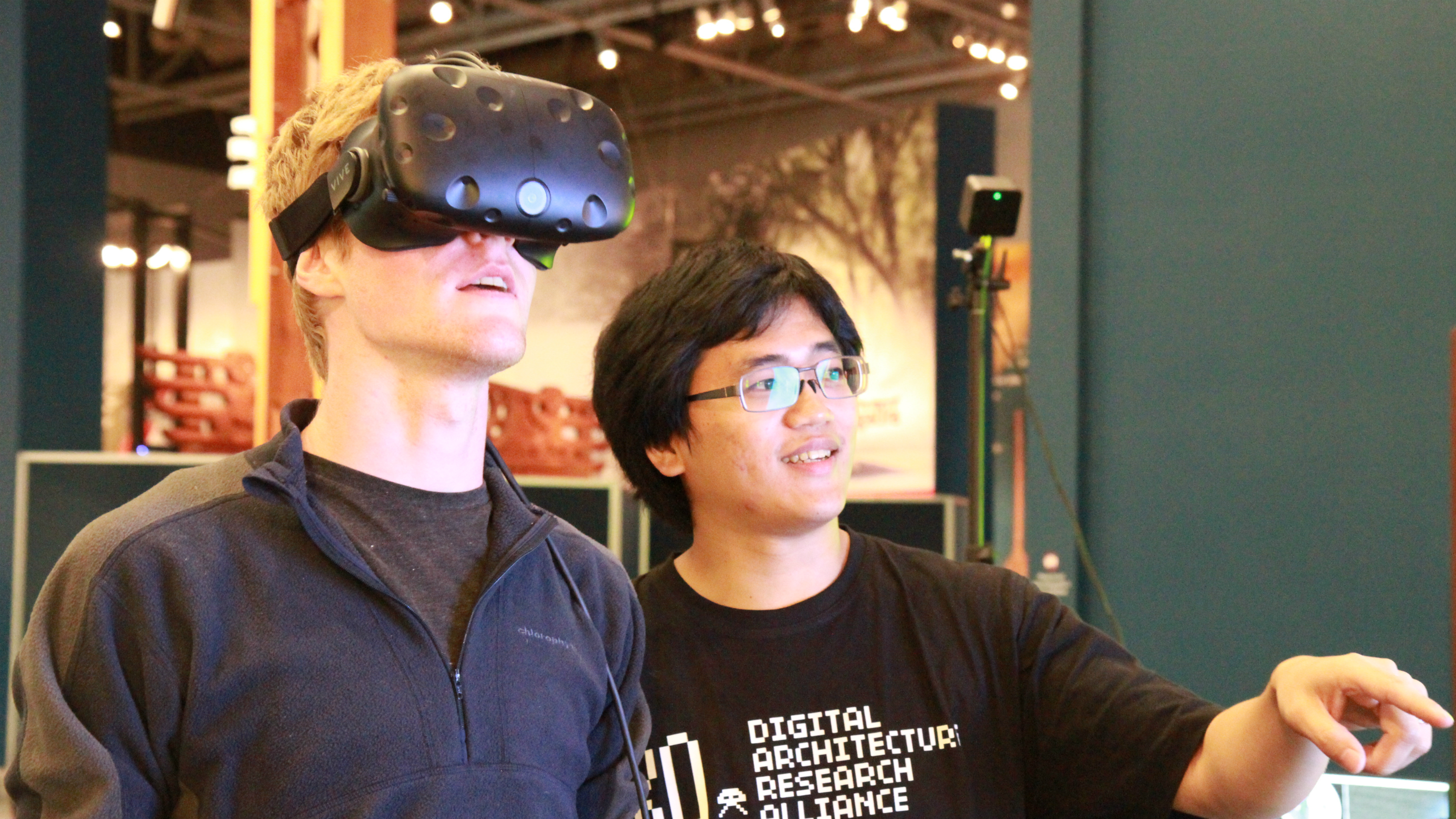 Architecture student Sky Lo talking a member of the public through what he is seeing through the VR headset